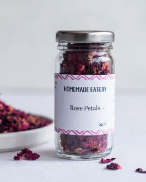 Dried Rose Petals in jar on table with plate behind
