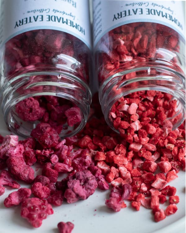 Freeze Dried Raspberries and Freeze Dried Strawberries in jars scattered on plate